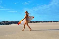Sund livsstil surfa konkurrensar som dyker pölsportar som simmar vatten Kvinna med surfingbrädan Royaltyfri Fotografi