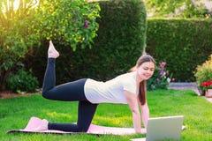 Sund livsstil ?va home G?ra kondition direktanslutet Härlig ung kvinna som utomhus gör sporten i trädgård royaltyfri foto