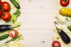 Sund livsstilbakgrund med olika färgrika grönsaker och örter som läggas ut i en ram en vit trätabell, utrymme för tex arkivfoto