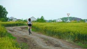 Sund livsstilkvinna som rider en cykel på den lantliga vägen lager videofilmer