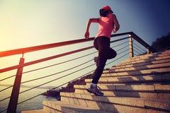 Sund livsstilsportkvinna som är rinnande upp på stentrappa Royaltyfri Fotografi