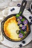 Sund lunch: hemlagad ostkaka med blåbär och ätliga blommor i tappning svärtar gjutjärnstekpannan på trä arkivbild