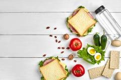 Sund lunchask med smörgåsar, ägg och nya grönsaker, flaska av vatten och muttrar på lantlig träbakgrund överkant Arkivfoto