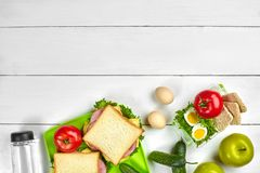 Sund lunchask med smörgåsar, ägg och nya grönsaker, flaska av vatten på lantlig träbakgrund Bästa sikt med Arkivbilder