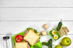 Sund lunchask med smörgåsar, ägg och nya grönsaker, flaska av vatten på lantlig träbakgrund Bästa sikt med Arkivfoto