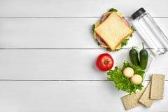 Sund lunchask med smörgåsen, ägg och nya grönsaker, flaska av vatten på lantlig träbakgrund Bästa sikt med Fotografering för Bildbyråer