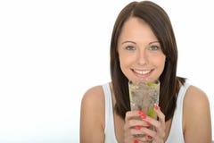 Sund lycklig naturlig ung kvinna som rymmer ett exponeringsglas av med is vatten med mogna limefrukt- och iskuber Arkivbild