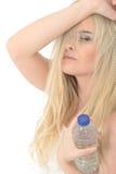 Sund lynnig trött ung blond kvinna som rymmer en flaska av mineralvatten Arkivbilder