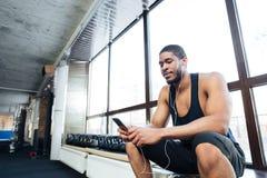 Sund man för kondition som använder smartphonen i idrottshallen royaltyfri bild