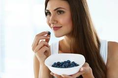 sund mat Den lyckliga kvinnan bantar på äta organiska blåbär Arkivfoton
