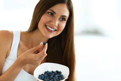 sund mat Den lyckliga kvinnan bantar på äta organiska blåbär Arkivbild