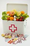 sund mat Första hjälpenask som fylls med frukter och grönsaker Arkivbild