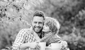 sund mat Fader- och pojkedrinkte utomhus Framkalla sunda matvanor Matning behandla som ett barn r royaltyfria foton