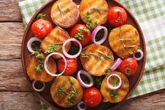 Sund mat: grillade potatisar och tomater med örter och löken Royaltyfria Bilder