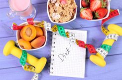 Sund mat, hantlar, m?ttband och anteckningsbok f?r anm?rkningar Banta, sund och sportig livsstil arkivbild