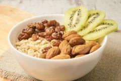 sund mat Havremjöl med kiwirussin och mandlar arkivbilder