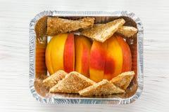 Sund mat i folieask, bantar begrepp Bakat äpple i den vita plattan Arkivbilder