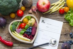 Sund mat i hjärtastetoskop och läkarundersökningreceptet bantar och medicinbegreppet arkivfoton