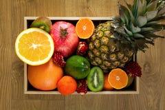 Sund mat i trämagasin: ananas, apelsin, tangerin, kiwi, granatäpple och grapefrukt Arkivbild