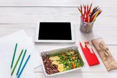 Sund mat, lunch i folieask på studenttabellen, bantar Arkivbilder