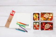 Sund mat, lunch i folieask på studenttabellen, bantar Arkivbild