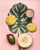 Sund mat, melon, mango och smoothies läggas ut på ett monsterablad, på en rosa bakgrund, den lekmanna- lägenheten arkivbild