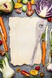 Sund mat och smaklig vegetarisk matlagningbakgrund med sortimentet av färgrika lantgårdgrönsaker runt om det tomma arket av pappe Royaltyfria Foton