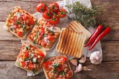 Sund mat: rostat bröd med vita bönor, tomater, ost och garli royaltyfri foto