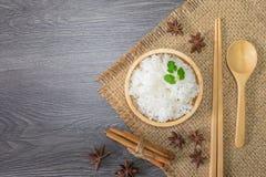 Sund mat, vita ris, lagat mat vitt ris, lagade mat vanliga ris i träbunke med kanel- och stjärnaanis, sked och pinnar, royaltyfri foto