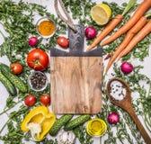 Sund matbakgrund med färgrika olika grönsaker för smaklig matlagning runt om skärbrädastället för text, ram på woode arkivfoton