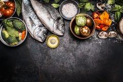 Sund matbakgrund med två doradofisches och grönsakingredienser för smaklig matlagning, bästa sikt royaltyfri fotografi