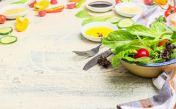 Sund maträtt för grön sallad med unga grönsallatsidor och olika dressingingredienser på ljus träbakgrund Arkivbild
