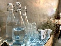 Sund mineralvatten i glasflaskor med en exponeringsglasuppsättning som förbereds på drinktabellen, klassikern och den gamla stile royaltyfria bilder
