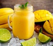 Sund mogen gul bananmangoSmoothie med skivor av limefrukt, mintkaramellen och is Royaltyfri Bild