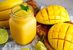 Sund mogen gul bananmangoSmoothie med skivor av limefrukt, mintkaramellen och is Arkivfoton