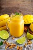 Sund mogen gul bananmangoSmoothie med skivor av limefrukt, mintkaramellen och is Fotografering för Bildbyråer