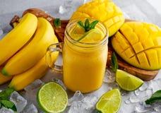 Sund mogen gul bananmangoSmoothie med skivor av limefrukt, mintkaramellen och is Royaltyfri Foto