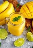 Sund mogen gul bananmangoSmoothie med skivor av limefrukt, mintkaramellen och is Sund mat för begrepp Royaltyfri Fotografi