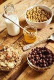 Sund morgonfrukost med olika typer av frukostsädesslag med honung och att mjölka på tabellen arkivfoton