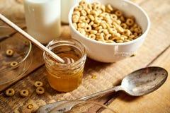 Sund morgonfrukostbunke mycket av honungflingor med honungskopan och att mjölka på trätabellen royaltyfria foton