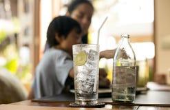Sund näring av dricksvatten med citronen och kvinnan arkivbild