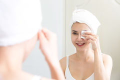 Sund ny flicka som tar bort makeup från hennes framsida med bomullsblocket Arkivfoton