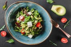 Sund ny sallad med avokadot, gr?splaner, arugula, spenat, k?rsb?rsr?da tomater och ost i platta ?ver den m?rka tabellen sund stri royaltyfria foton