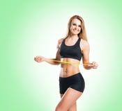 Sund och sportig kvinna för passform, i sportswear som mäter hennes kropp I arkivfoton