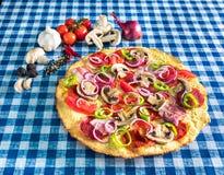 Sund pizza med salamichampinjonen och grönsaker royaltyfria bilder