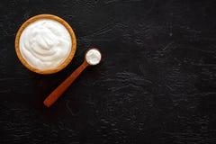 Sund produkt, sunt mål Grekisk yoghurt i near sked för brun bunke på svart utrymme för kopia för bästa sikt för bakgrund royaltyfri foto