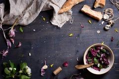 Sund purpurfärgad salladblandning med nytt franskt bröd över den lantliga trätabellen, från över Bakgrundsorientering med spac fö Fotografering för Bildbyråer