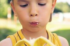Sund pys som äter bananaonnaturbakgrund Den lyckliga ungen tycker om att äta ny frukt Arkivfoton