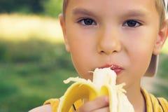 Sund pys som äter bananaonnaturbakgrund Den lyckliga ungen tycker om att äta ny frukt Royaltyfria Bilder