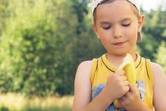 Sund pys som äter bananen Den lyckliga ungen tycker om att äta ny frukt Arkivbild